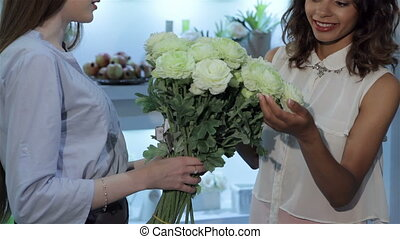 Florist gives the bouquet to the young woman - Young female...