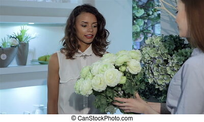 Female buyer examines the bouquet of roses