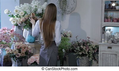 Female florist inspecting flowers at her flower shop -...