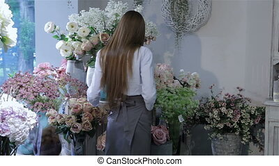 Female florist rearranges flowers at flower shop - Young...