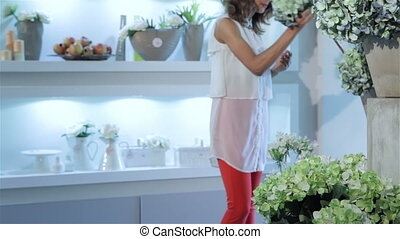 Woman chooses bouquets of flowers at flower shop - Pretty...