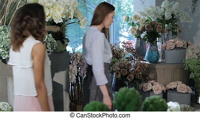 Two women come into flower shop - Two young women coming...