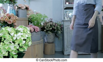 Female florist squats down near the vase with flowers -...
