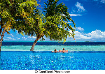 young couple relaxing in infinity pool under coco palms in...