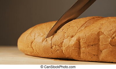 Close-up of freshly baked bread cut with a kitchen knife on...