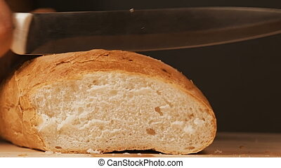 Cutting freshly baked bread - Baker is cutting freshly baked...
