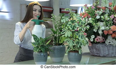 Female florist watering plants at flower shop - Caucasian...