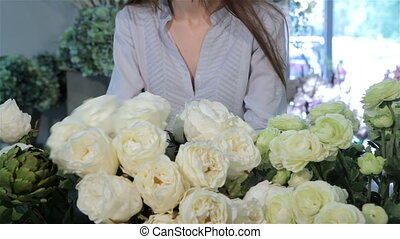 Female hands moves white roses at flower shop - Close up of...