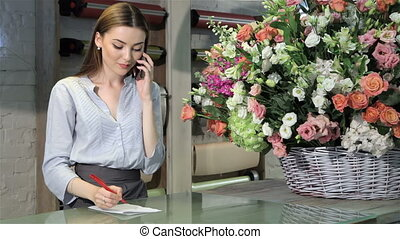 Female florist accepts order for bouquet of flowers at...