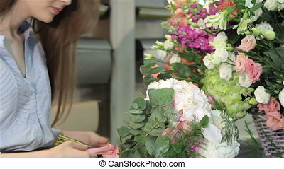 Female florist makes a bouquet of flowers at flower shop -...