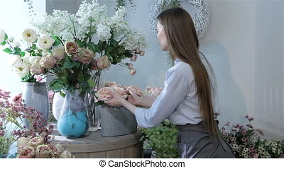 Female florist moving flowers near the window at flower shop