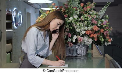 Female florist talks on the phone at flower shop - Side view...