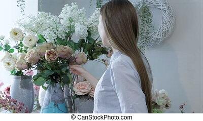 Female florist arranges flowers in vases at flower shop -...