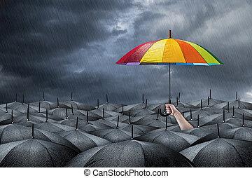 rainbow umbrella concept - rainbow umbrella in mass of black...