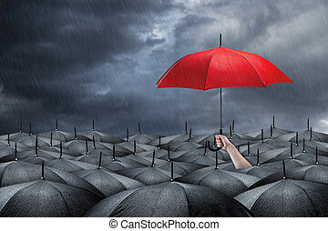 red umbrella concept - red umbrella in mass of black...