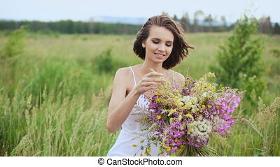 Happy young girl with a bouquet of wild flowers in his hand.
