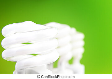 three compact fluorescent light bulbs on green background