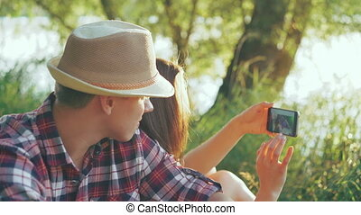 Young couple taking selfie on the nature near the tree. 4k