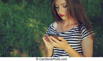 Young girl using phone in the green summer park. 4k