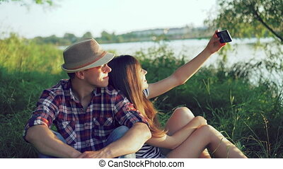 Young couple taking selfie on the nature near the pond. 4k
