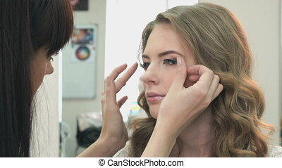 Makeup artist sticks the eyelashes to the girl - Makeup...