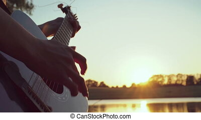 Close up of girl's hands playing guitar near the evening pond. 4k