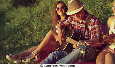 Two girl with funny boy rejoicing with guitar on the nature...