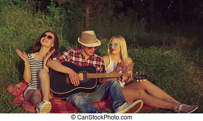 Two girl with funny boy rejoicing with guitar in the sunny...