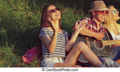 Two girl with funny boy rejoicing with guitar in the sunny park. Slow motion