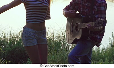 Young girl dancing when boy playing guitar near the lake...