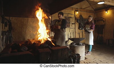 Forge master and journeyman woman unfetters metal rod....