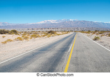 Andean road crossing a barren landscape at high altitude,...