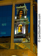Salta cathedral tower reflected in a modern building facade...