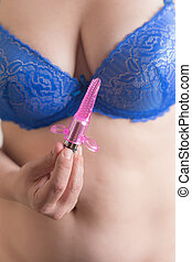 woman holding a small purple vibrator - woman in bra holding...