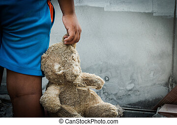 Poor child holding a teddy bear