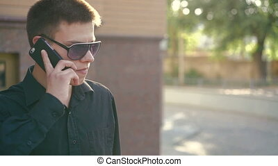 Young businessman speaking on the phone and smoking...