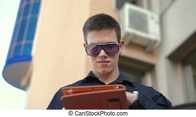Young successful businessman using tablet outdoor near the office