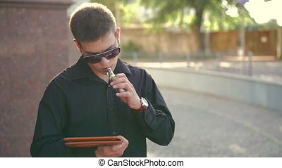 Style man smoking electronic cigarette and using a tablet outdoor