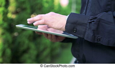 Man's hands touching and using tablet on green tree...