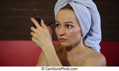 Woman dressed in a bath towel makes a make-up. Skin care....