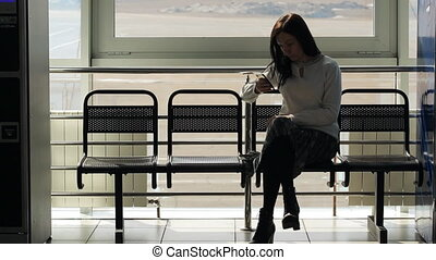 The woman is sitting in airport waiting hall waiting for someone
