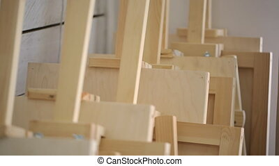 Many wooden easels stands near wall in art studio. Wall is...