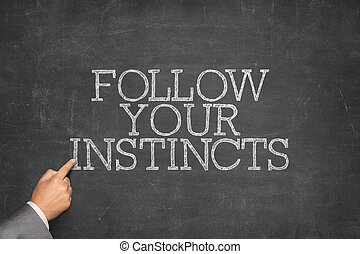 Follow Your Instincts text on blackboard with businessman...