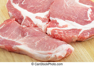 Raw meat steaks on wooden board background, DOF