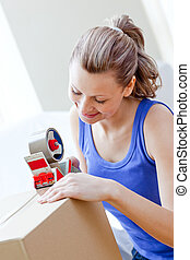 Beautiful woman packing boxes in the living-room