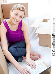 Smiling woman using a laptop in the living-room