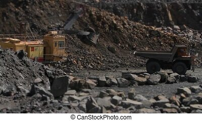 Excavator loads a stone in the heavy truck in the quarry...