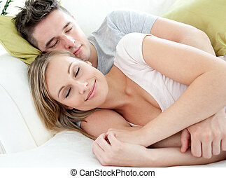 Relaxed lovers having fun together on a sofa in the...