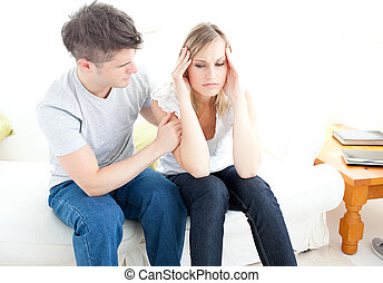 Exhausted couple having an argue together in the living-room