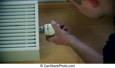 Man's hand adjusting radiator temperature. - Man's hand...